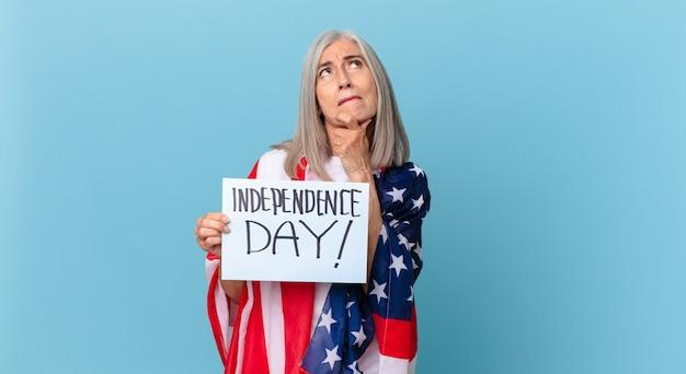 Kobieta w średnim wieku z siwymi włosami myśli, ma wątpliwości i jest zdezorientowana. koncepcja dnia niepodległości