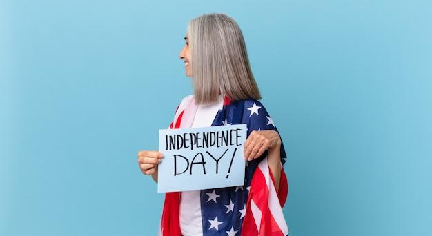 Kobieta W średnim Wieku Z Siwymi Włosami Na Widoku Profilu Myśląca, Wyobrażająca Sobie Lub Marząca. Koncepcja Dnia Niepodległości Premium Zdjęcia