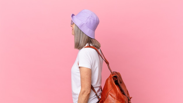 Kobieta w średnim wieku z siwymi włosami na widoku profilu myślenie, wyobrażanie sobie lub marzenie. koncepcja lato