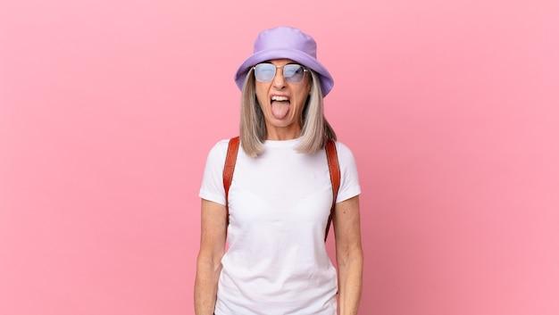 Kobieta w średnim wieku z siwymi włosami o pogodnym i buntowniczym nastawieniu, żartująca i wystawiająca język. koncepcja lato