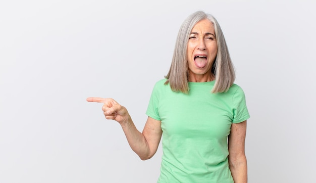 Kobieta w średnim wieku z siwymi włosami o pogodnym i buntowniczym nastawieniu, żartuje, wystawia język i wskazuje na bok