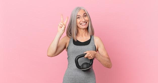 Kobieta w średnim wieku z siwymi włosami podnosząca hantle. koncepcja fitness