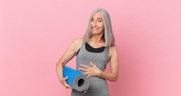 Kobieta w średnim wieku z siwymi włosami śmiejąca się głośno z jakiegoś przezabawnego żartu i trzymająca matę do jogi. koncepcja fitness