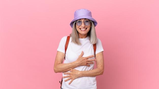 Kobieta w średnim wieku z siwymi włosami śmiejąca się głośno z jakiegoś zabawnego żartu. koncepcja lato