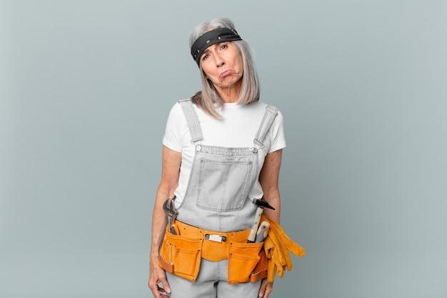 Kobieta w średnim wieku z siwymi włosami, smutna i jęcząca, z nieszczęśliwym spojrzeniem i płaczem, nosząca odzież roboczą i narzędzia. koncepcja sprzątania