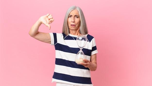 Kobieta w średnim wieku z siwymi włosami trzymająca zegar z klepsydrą