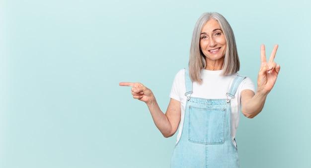 Kobieta w średnim wieku z siwymi włosami uśmiecha się i wygląda na szczęśliwą, gestykulując zwycięstwo lub pokój i wskazując na bok