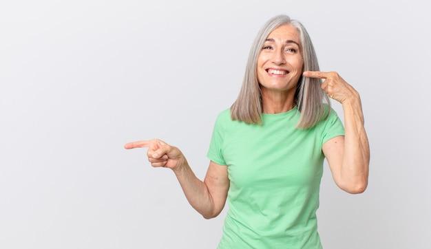 Kobieta w średnim wieku z siwymi włosami uśmiecha się pewnie, wskazując na swój szeroki uśmiech i wskazując na bok