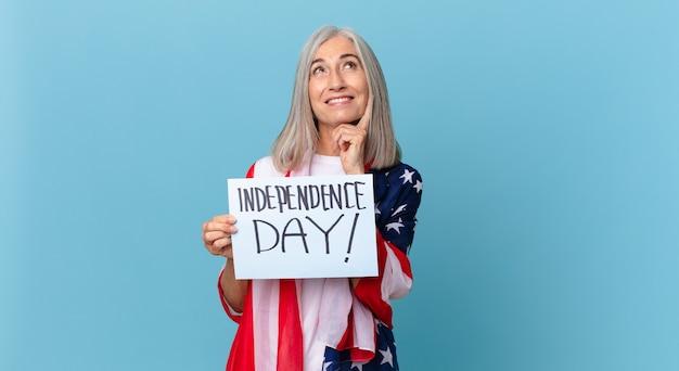 Kobieta w średnim wieku z siwymi włosami uśmiecha się radośnie i marzy lub wątpi. koncepcja dnia niepodległości