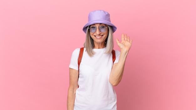 Kobieta w średnim wieku z siwymi włosami uśmiecha się radośnie, macha ręką, wita i wita. koncepcja lato