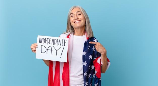 Kobieta W średnim Wieku Z Siwymi Włosami Uśmiechając Się Radośnie, Czując Się Szczęśliwa I Wskazując Na Bok. Koncepcja Dnia Niepodległości Premium Zdjęcia