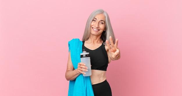 Kobieta w średnim wieku z siwymi włosami, uśmiechnięta i przyjazna, pokazująca numer trzy z ręcznikiem i bidonem. koncepcja fitness
