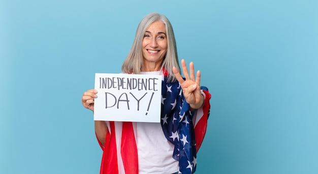 Kobieta w średnim wieku z siwymi włosami uśmiechnięta i wyglądająca przyjaźnie, pokazując cyfrę cztery. koncepcja dnia niepodległości