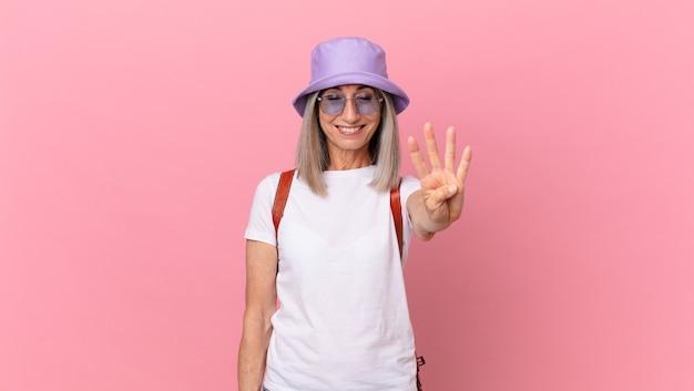 Kobieta w średnim wieku z siwymi włosami, uśmiechnięta i wyglądająca przyjaźnie, pokazując cyfrę cztery. koncepcja lato