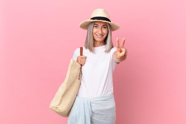 Kobieta w średnim wieku z siwymi włosami, uśmiechnięta i wyglądająca przyjaźnie, pokazując numer dwa. koncepcja lato