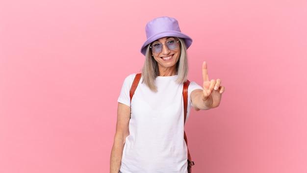 Kobieta w średnim wieku z siwymi włosami, uśmiechnięta i wyglądająca przyjaźnie, pokazując numer jeden. koncepcja lato