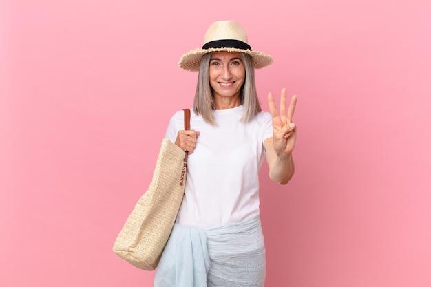 Kobieta w średnim wieku z siwymi włosami uśmiechnięta i wyglądająca przyjaźnie, pokazując numer trzy. koncepcja lato