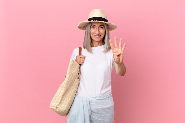 Kobieta w średnim wieku z siwymi włosami uśmiechnięta i wyglądająca przyjaźnie, pokazująca numer cztery. koncepcja lato