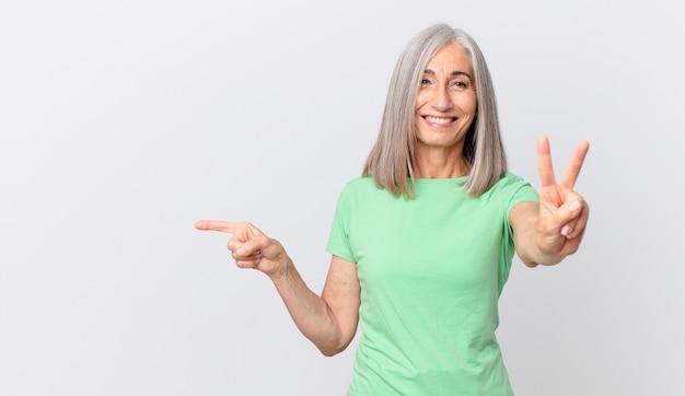 Kobieta w średnim wieku z siwymi włosami, uśmiechnięta i wyglądająca przyjaźnie, pokazująca numer dwa i wskazująca na bok