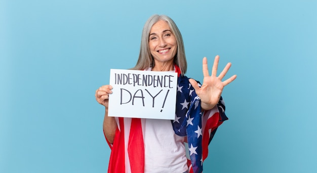 Kobieta w średnim wieku z siwymi włosami uśmiechnięta i wyglądająca przyjaźnie, pokazująca numer pięć. koncepcja dnia niepodległości