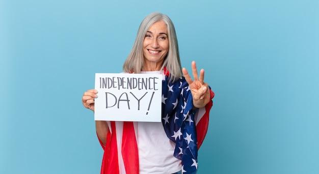 Kobieta w średnim wieku z siwymi włosami uśmiechnięta i wyglądająca przyjaźnie, pokazująca numer trzy. koncepcja dnia niepodległości
