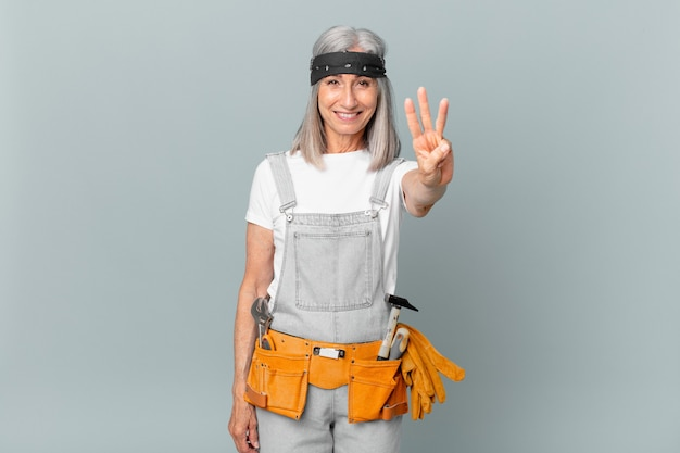 Kobieta w średnim wieku z siwymi włosami, uśmiechnięta i wyglądająca przyjaźnie, pokazująca numer trzy, nosząca odzież roboczą i narzędzia. koncepcja sprzątania