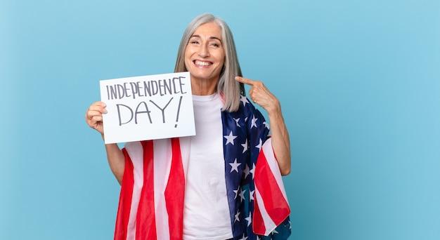 Kobieta w średnim wieku z siwymi włosami, uśmiechnięta pewnie, wskazując na swój szeroki uśmiech. koncepcja dnia niepodległości
