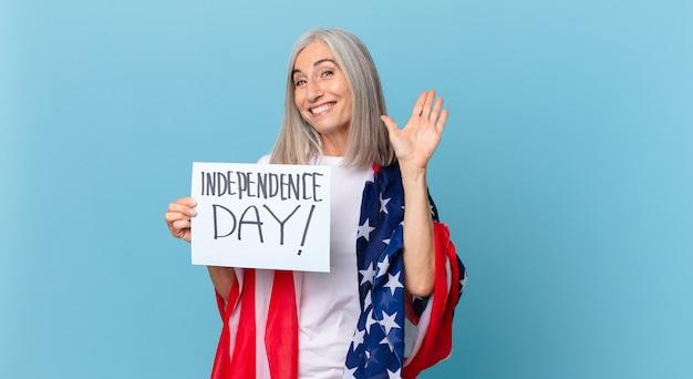 Kobieta w średnim wieku z siwymi włosami, uśmiechnięta radośnie, machająca ręką, witająca i pozdrawiająca. koncepcja dnia niepodległości