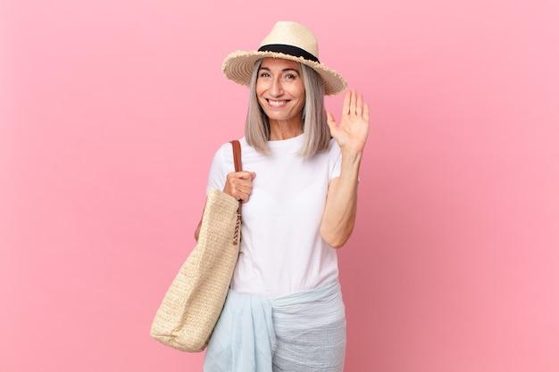 Kobieta w średnim wieku z siwymi włosami, uśmiechnięta radośnie, machająca ręką, witająca i pozdrawiająca. koncepcja lato