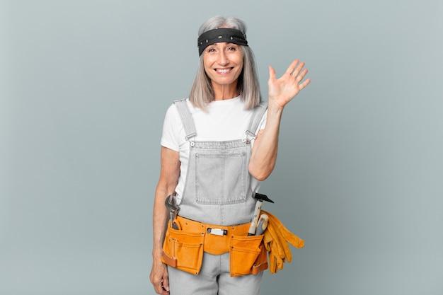 Kobieta w średnim wieku z siwymi włosami, uśmiechnięta radośnie, machająca ręką, witająca i witająca cię, ubrana w strój roboczy i narzędzia. koncepcja sprzątania