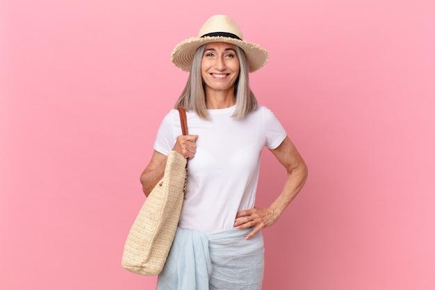 Kobieta w średnim wieku z siwymi włosami, uśmiechnięta radośnie z ręką na biodrze i pewna siebie. koncepcja lato