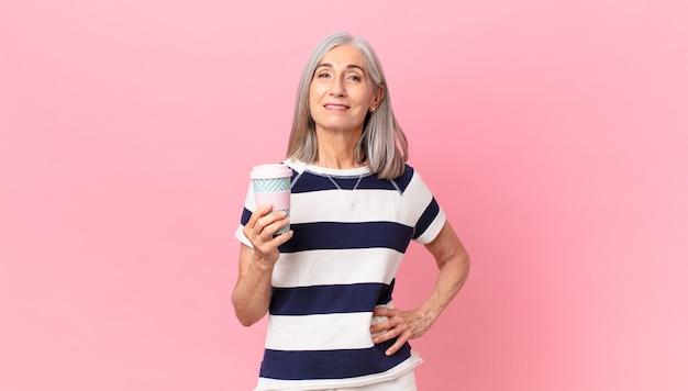 Kobieta w średnim wieku z siwymi włosami, uśmiechnięta radośnie z ręką na biodrze i pewna siebie, trzymająca pojemnik na kawę na wynos