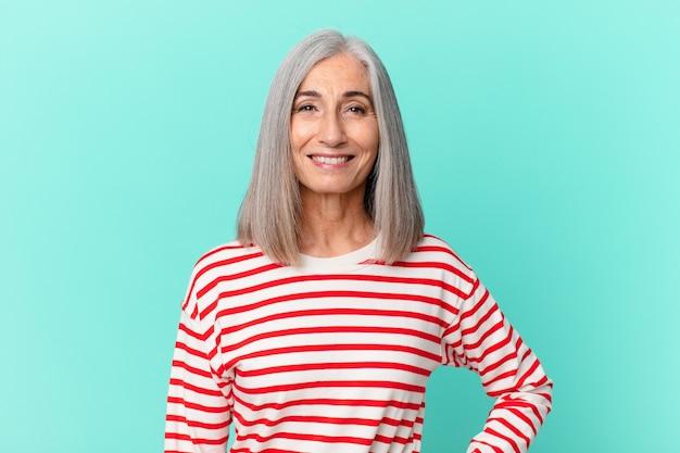 Kobieta w średnim wieku z siwymi włosami, uśmiechnięta radośnie z ręką na biodrze i pewna siebie