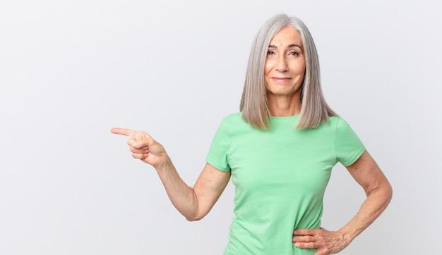 Kobieta w średnim wieku z siwymi włosami, uśmiechnięta radośnie z ręką na biodrze, pewna siebie i wskazująca na bok
