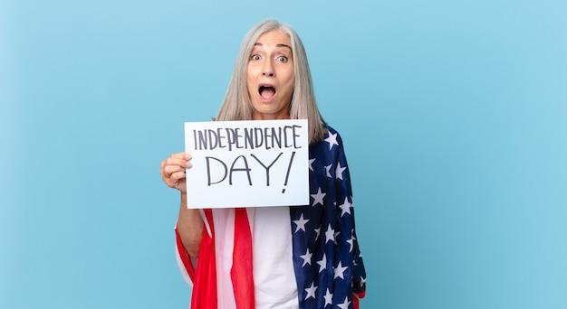 Kobieta w średnim wieku z siwymi włosami wygląda na bardzo zszokowaną lub zaskoczoną