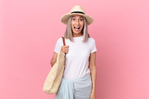 Kobieta w średnim wieku z siwymi włosami wygląda na bardzo zszokowaną lub zdziwioną. koncepcja lato