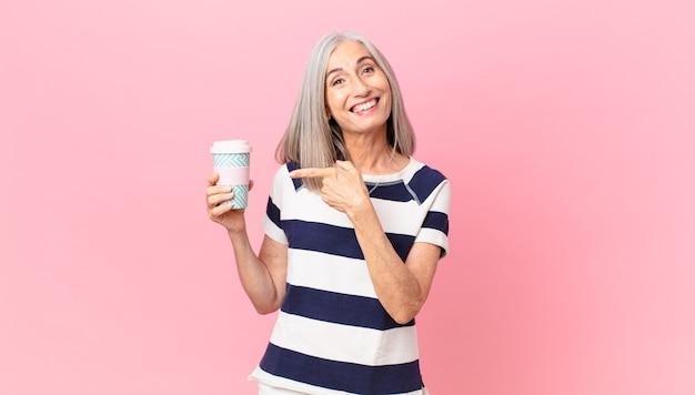 Kobieta w średnim wieku z siwymi włosami wygląda na podekscytowaną i zaskoczoną, wskazując na bok i trzymająca pojemnik na kawę na wynos