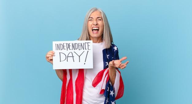 Kobieta w średnim wieku z siwymi włosami wygląda na rozgniewaną, zirytowaną i sfrustrowaną. koncepcja dnia niepodległości