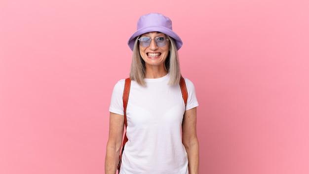 Kobieta w średnim wieku z siwymi włosami wygląda na szczęśliwą i mile zaskoczoną. koncepcja lato