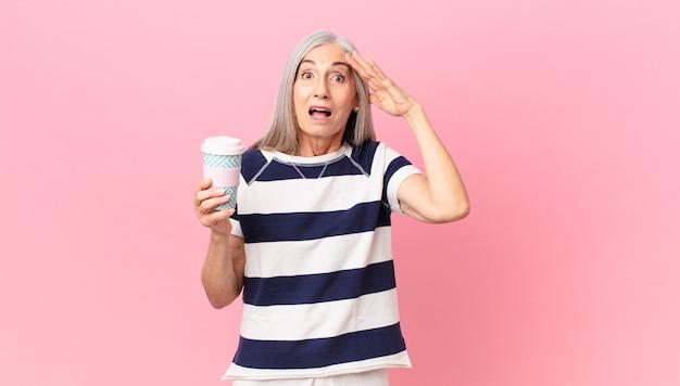 Kobieta w średnim wieku z siwymi włosami wygląda na szczęśliwą, zdumioną i zaskoczoną i trzyma pojemnik na kawę na wynos