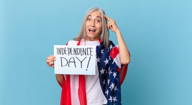 Kobieta w średnim wieku z siwymi włosami wygląda na szczęśliwą, zdumioną i zdziwioną. koncepcja dnia niepodległości
