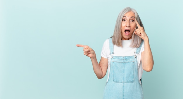 Kobieta w średnim wieku z siwymi włosami wygląda na zaskoczoną, realizując nową myśl, pomysł lub koncepcję i wskazując na bok