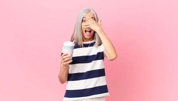 Kobieta w średnim wieku z siwymi włosami wygląda na zaszokowaną, przestraszoną lub przerażoną, zakrywa twarz dłonią i trzyma pojemnik na kawę na wynos