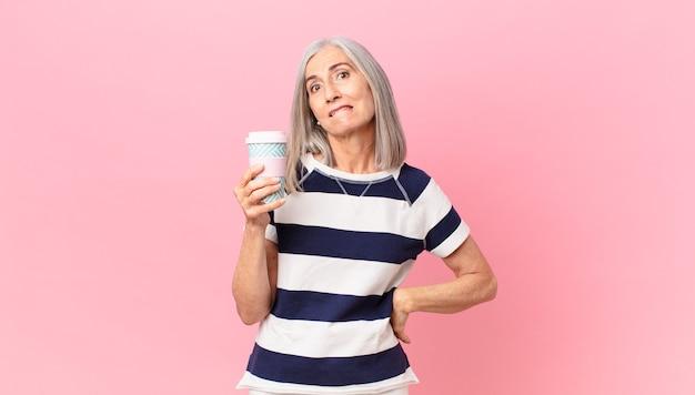 Kobieta w średnim wieku z siwymi włosami wygląda na zdziwioną i zdezorientowaną i trzyma pojemnik na kawę na wynos
