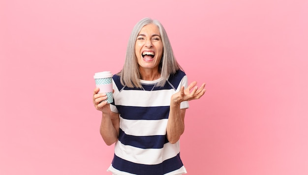 Kobieta w średnim wieku z siwymi włosami wygląda na złą, zirytowaną i sfrustrowaną i trzyma pojemnik na kawę na wynos