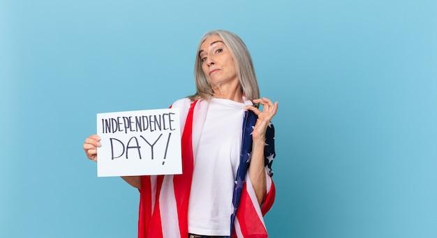 Kobieta w średnim wieku z siwymi włosami wyglądająca arogancko, odnosząca sukcesy, pozytywna i dumna. koncepcja dnia niepodległości