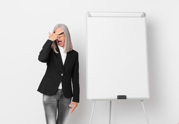 Kobieta w średnim wieku z siwymi włosami wyglądająca na zaszokowaną, przestraszoną lub przerażoną, zakrywającą twarz dłonią i miejscem na kopię na desce. pomysł na biznes