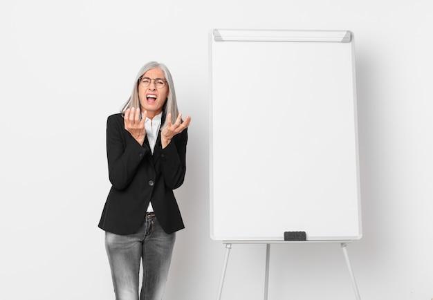 Kobieta w średnim wieku z siwymi włosami wyglądająca na zdesperowaną, sfrustrowaną i zestresowaną, a na desce kopia przestrzeń. pomysł na biznes