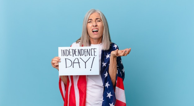Kobieta w średnim wieku z siwymi włosami, wyglądająca na zdesperowaną, sfrustrowaną i zestresowaną. koncepcja dnia niepodległości