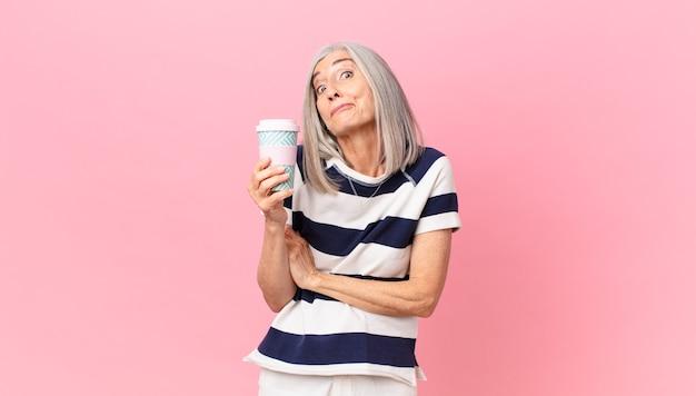 Kobieta w średnim wieku z siwymi włosami wzrusza ramionami, czuje się zdezorientowana i niepewna oraz trzyma pojemnik na kawę na wynos